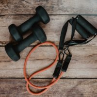 WFH workouts: dumb bells, elastic workout band on wood floor Photo by Kelly Sikkema on Unsplash